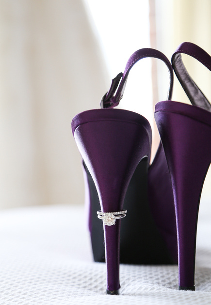 Wedding photography, a pair of deep purple high heels with a diamond engagement ring on the left heel.