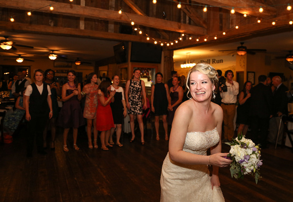 Wedding photography, a bride smiles playfully just before she tosses her bouquet.