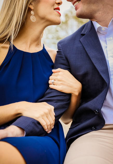 Engagement photography, a closeup of a couple's arms intertwined. She wears a diamond ring. They are smiling at each other.
