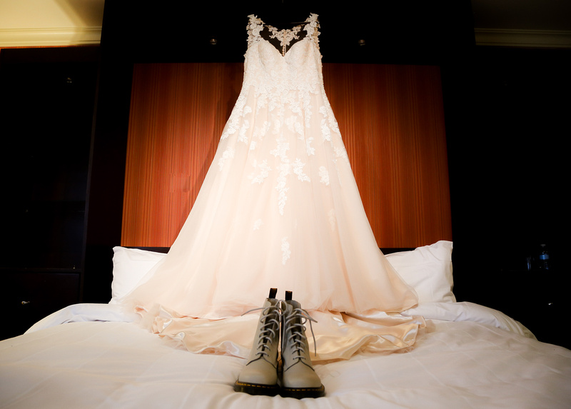 Wedding photography, a white lace gown hangs in front of a red wall, with white Doc Martins in front.
