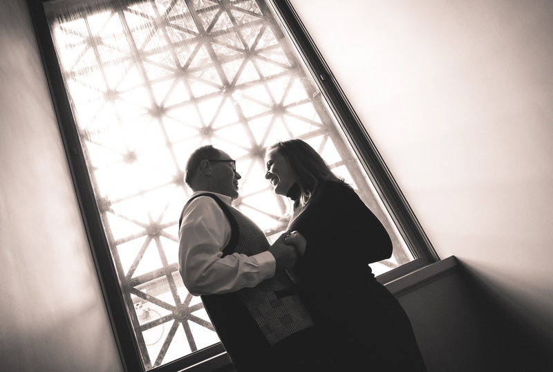 Engagement photography, a couple holds hands and smiles in front of a large window.