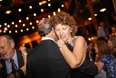 Wedding photography, a woman with curly hair dances tenderly with her husband.