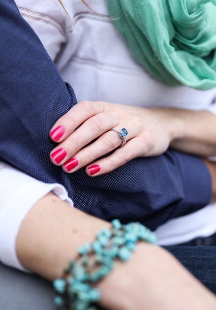 Engagement photography, a closeup of a woman's hands wearing an engagement ring with a blue stone.