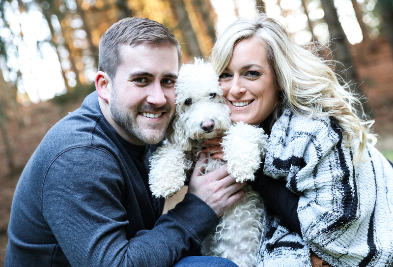 Engagement photography, a couple holds up their little white dog and smiles right next to his face.
