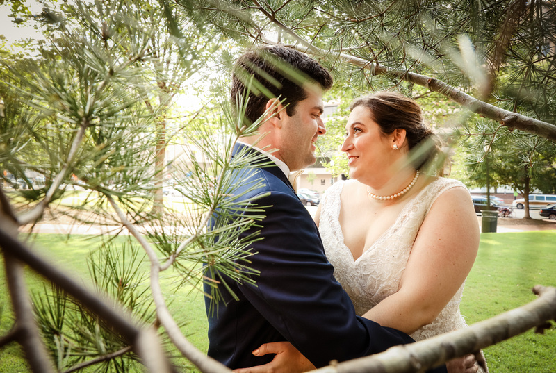 Wedding photography, a bride and groom gaze at each other romantically in an evergreen tree.
