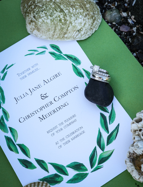 Wedding photography, a wedding invitation with green accents and seashells. The wedding rings balance on a rock.