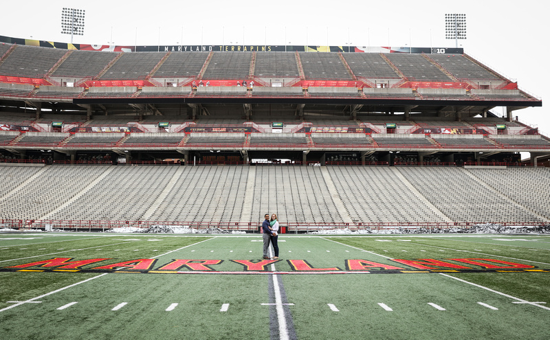 Engagement photography, a couple stands together on the University of MD football field.