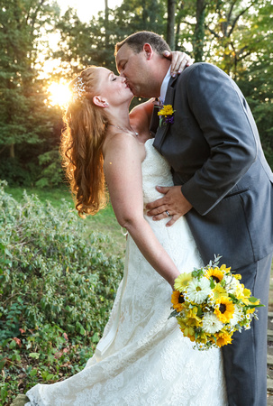 Wedding photography, the groom dips the bride and kisses her. She is holding yellow flowers.