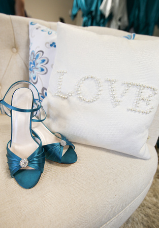 Wedding photography, the bride's teal high heels sitting on a chair with a pillow that says love.