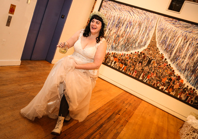 Wedding photography, the bride laughs and dances, showing the leggings and boots under her dress.