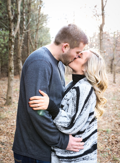 Engagement photography, a couple kisses passionately in the woods. She wear a black and grey sweater.
