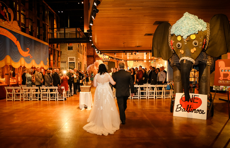 Wedding photography, a father walks his daughter down the aisle in a colorful art museum.