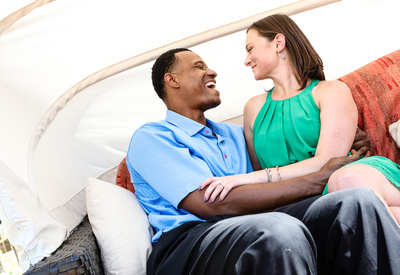 Engagement photography: a man in a blue shirt laughs adoringly at his fiancé, they sit on a red couch.