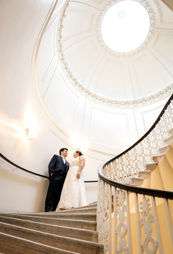 Wedding photography, a bride and groom stand together on a spiral staircase with an open ceiling.