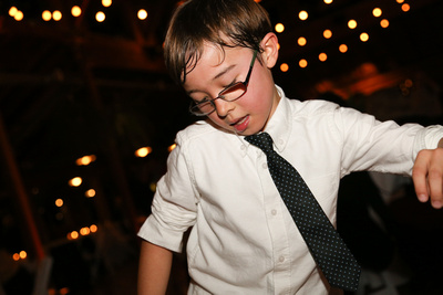 Wedding photography, a little boy dances in a white shirt with a black tie.