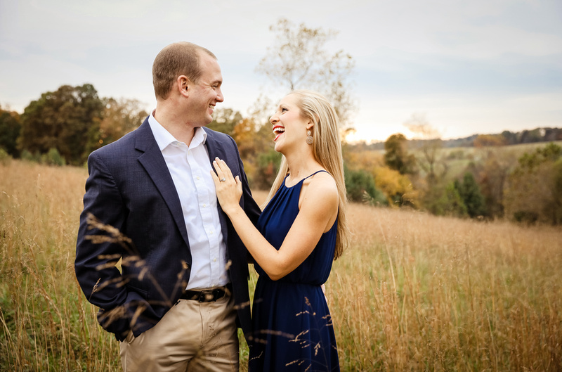 Engagement photography, a young lady laughs with love as she places her hand on her fiance's chest.