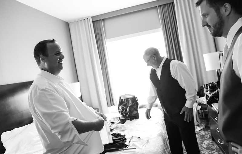 Wedding photography, a groom smiles while getting dressed for his wedding day.