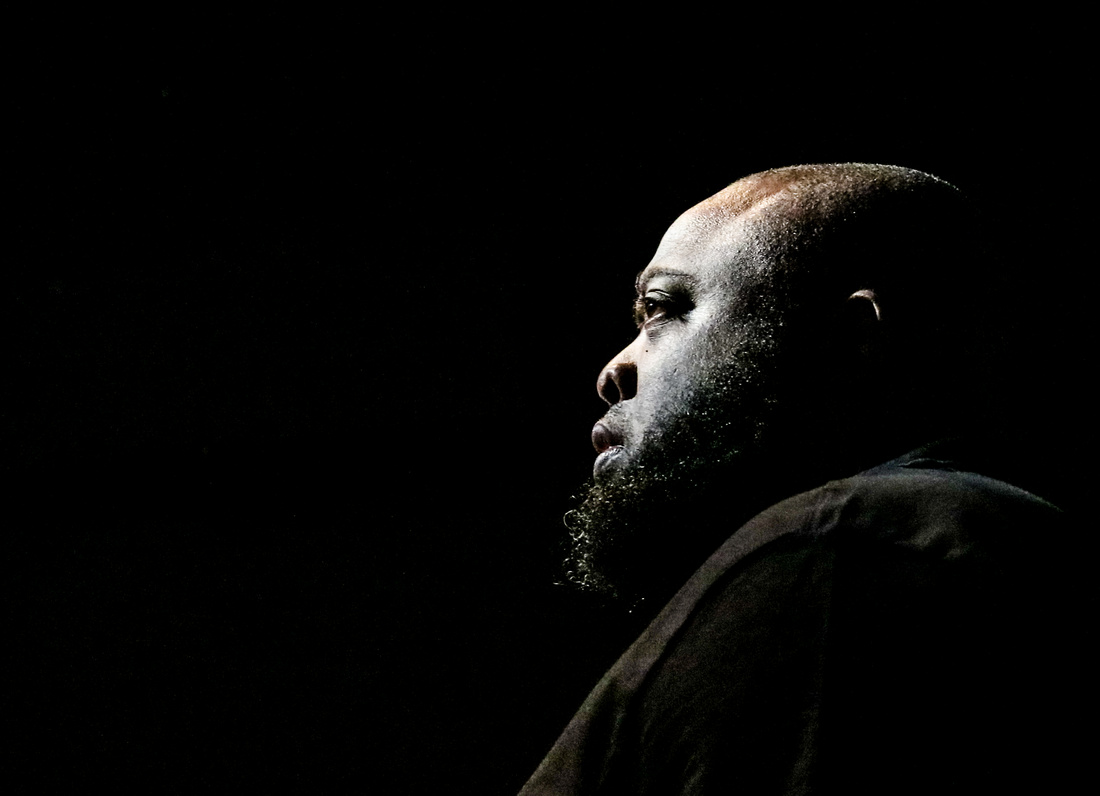 Completely black background. In the foreground is the profile of an African American man face lit by one stage light. 2016 in photos.