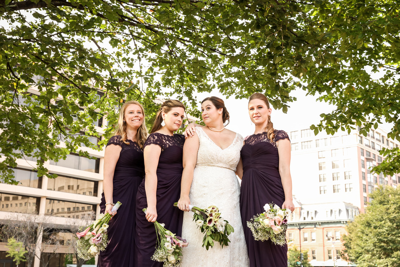 Wedding photography, a bride and bridesmaids pose under a tree in purple gowns.