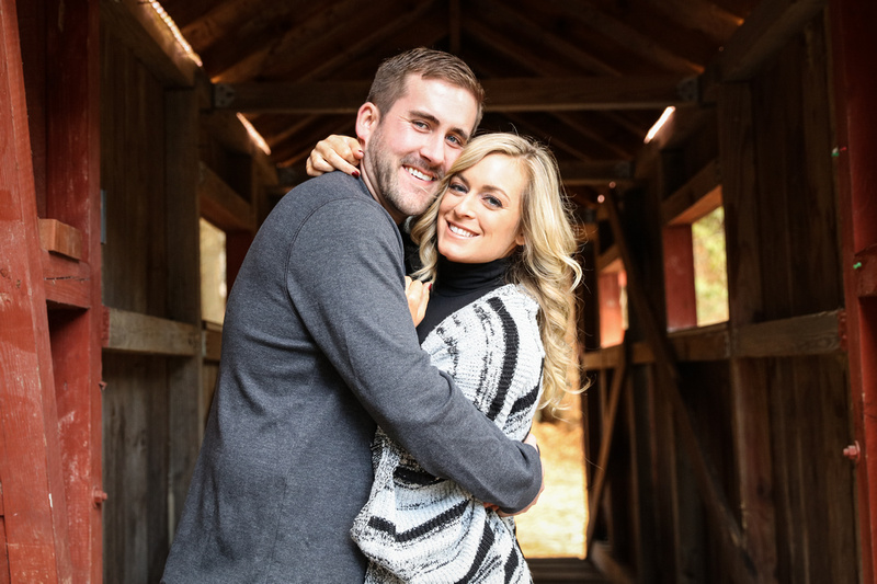 Engagement photography, a blond woman and man embrace under a red covered bridge.