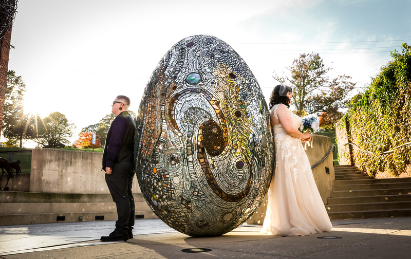 Wedding photography, a bride and groom stand back to back next to a large stained glass egg.