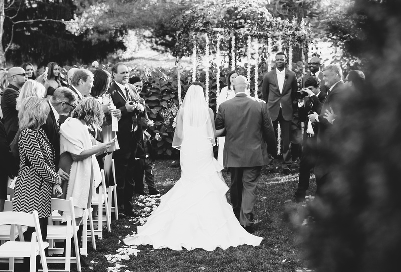 Wedding photography, a black and white image of a bride and her father walking down the aisle.