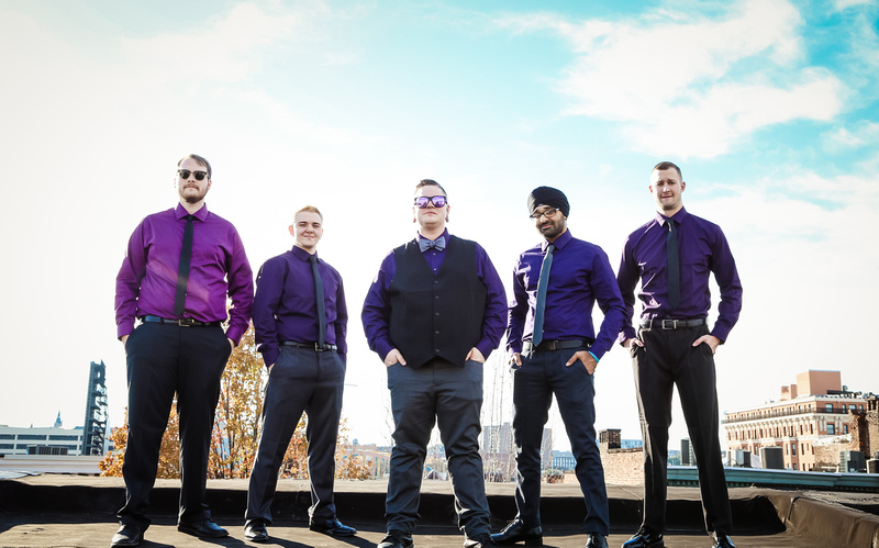 Wedding photography, a groom and groomsmen in purple shirts pose on a Baltimore rooftop.