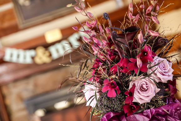 Wedding photography, a bouquet of purple and lavender flowers on a table. A Mr. and Mrs. sign is in the background.