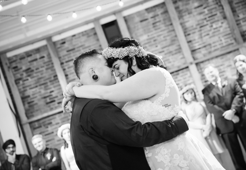 Wedding photography, a black and white image of a bride and groom resting their foreheads together during their first dance.