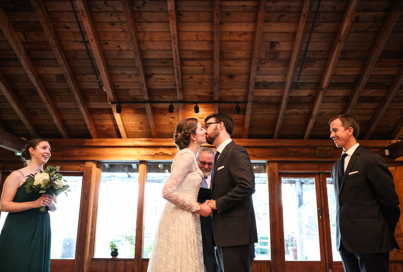 Wedding photography, a bride and groom share their first kiss in a log cabin venue.