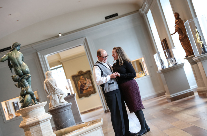 Engagement photography, a couple holds hands and smiles in an empty art museum.