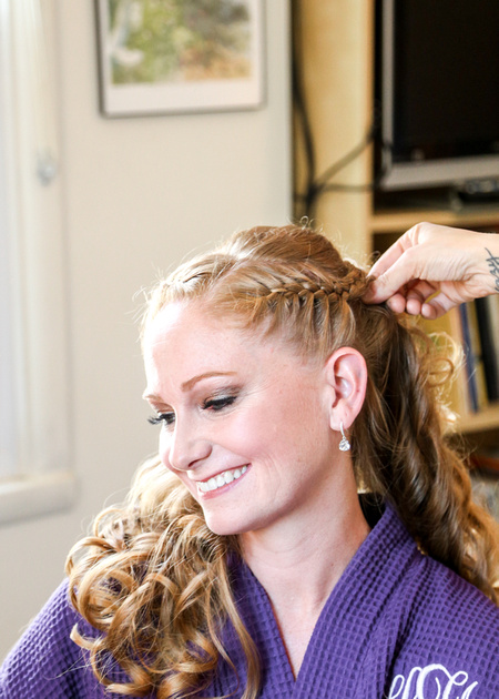 Wedding photography, a bride in a purple robe smiles contentedly while her hair is braided.