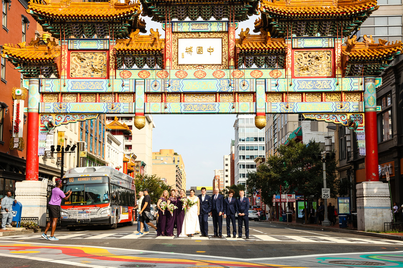Wedding photography, a wedding party stands underneath the Chinatown archway in DC.