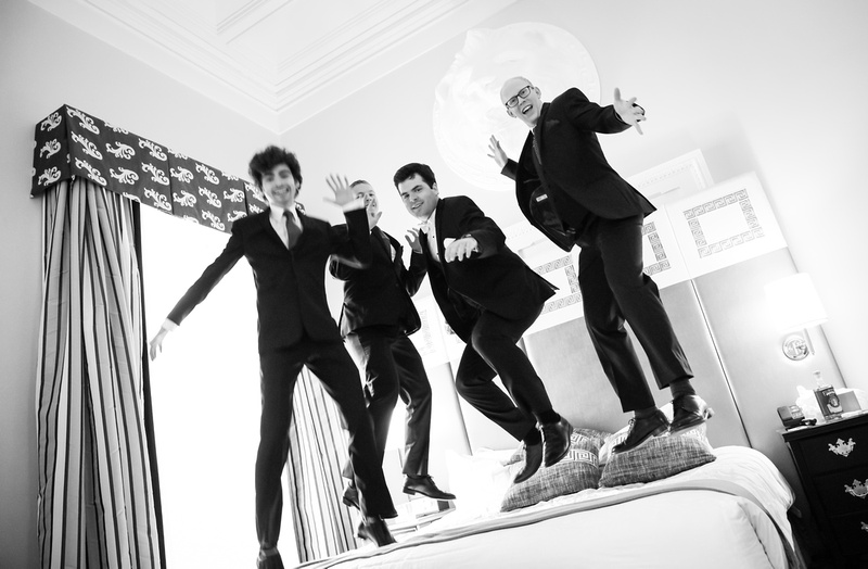 Wedding photography, a groom and his groomsmen jump on the bed in their wedding suits.