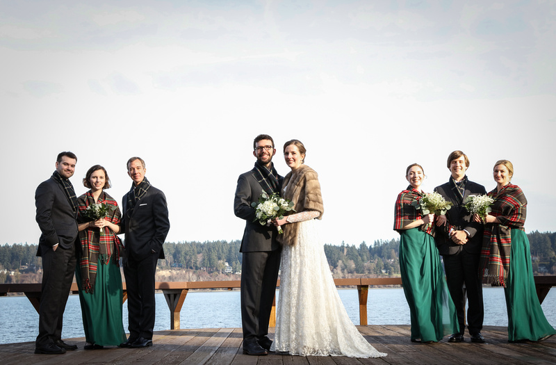 Wedding photography, a wedding party  standing on a dock by the water. They wear green and plaid.