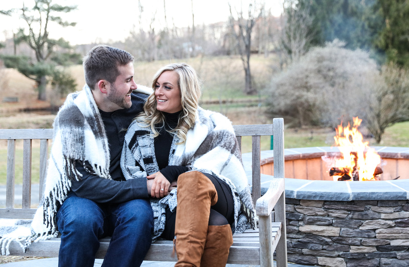 Engagement photography, a couple snuggles on a bench, sitting by an outdoor fire pit.