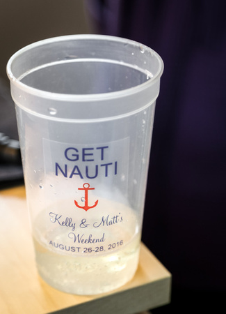 "Wedding photography, a plastic cup that says ""Get Nauti"" with a red anchor and the bride and groom's names."
