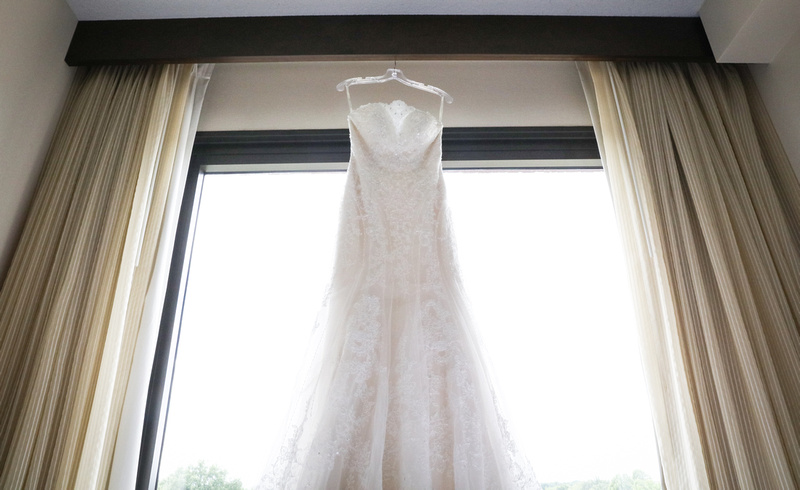 Wedding photography, a white bridal gown hangs in a picture window with beige curtains.