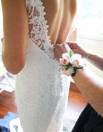 Wedding photography, a mother's hands button a bride's low cut lace white gown.