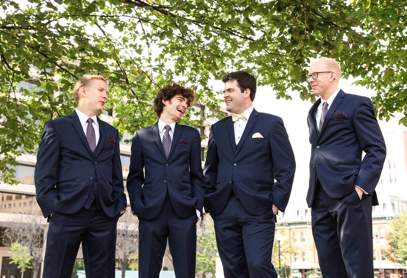 Wedding photography, a groom and groomsmen smile in navy blue suits under a tree limb.