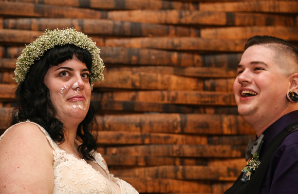 Wedding photography, a bride makes a face after her groom puts cake on her face, the groom is laughing.