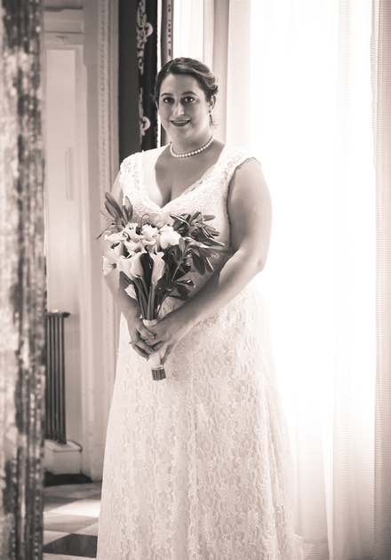 Wedding photography, a bride in a lace gown holding white tulips.