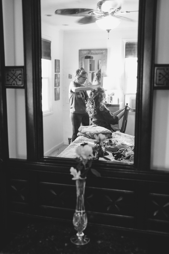 Wedding photography, a reflection shot in a mirror. A bride sits in a chair having her long curly hair styled.