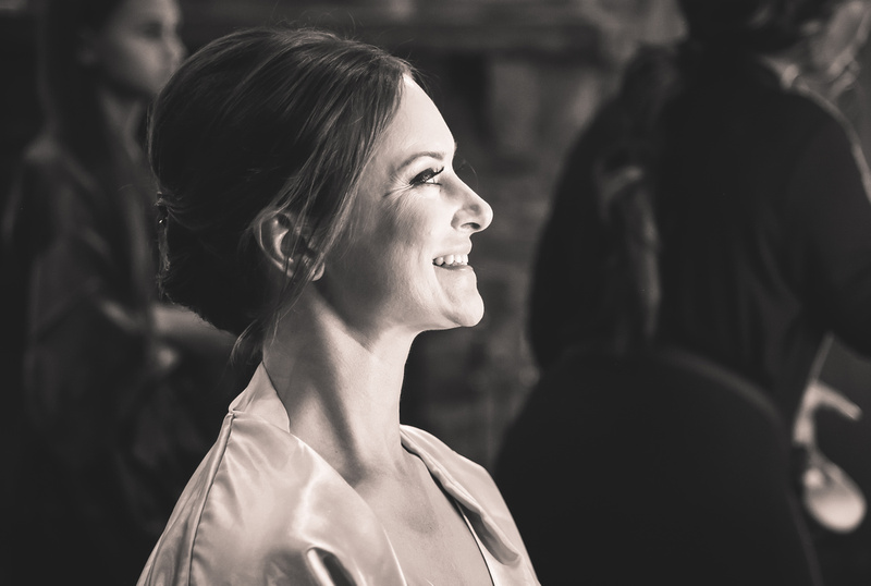 Wedding photography, a black and white image of a bride in profile, smiling.