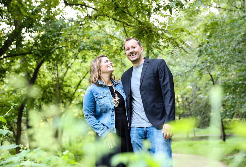 Family photography: a couple wearing jeans and black stand in the green woods, they are laughing.