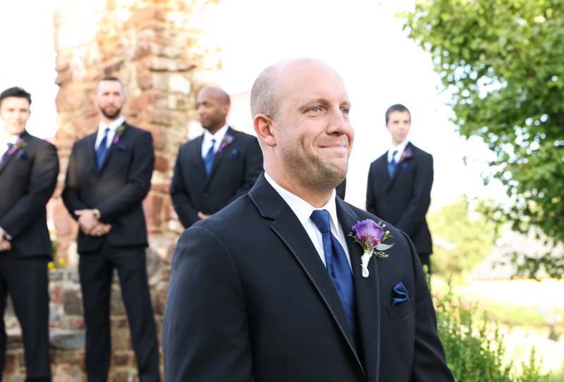 Wedding photography, a groom fights back tears as he watches his bride walk down the aisle.