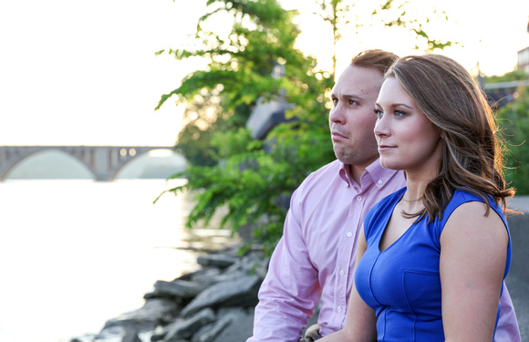 A young woman in a blue dress gazes out at the water. Her fiancé is making silly faces behind her. engagement photography