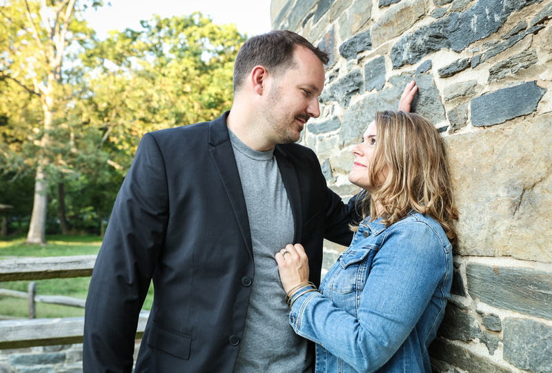 Family photography: a couple leans against a stone wall and looks at each other romantically.