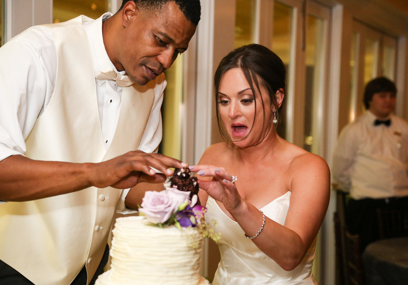 Wedding photography, the bride is nervous while cutting the cake with the groom.