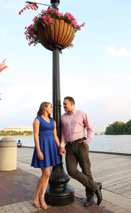A couple stands by the waterfront, leaning on a black lamp post with pink flowers. engagement photography
